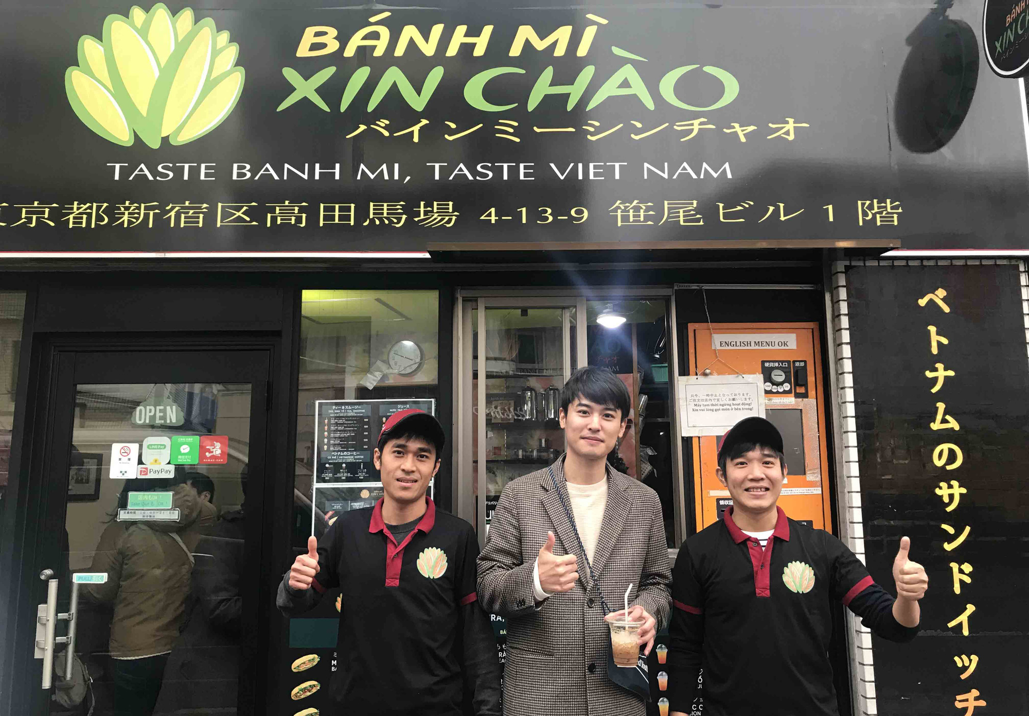 Japanese actor Horii Arata (center) from the national broadcaster NHK poses with Vietnamese brothers Bui Thanh Tam and Bui Thanh Duy in front of one of the duo's Banh Mi Xin Chao stores in Tokyo, Japan in a supplied photo taken in early 2020. Photo: Duy Tam