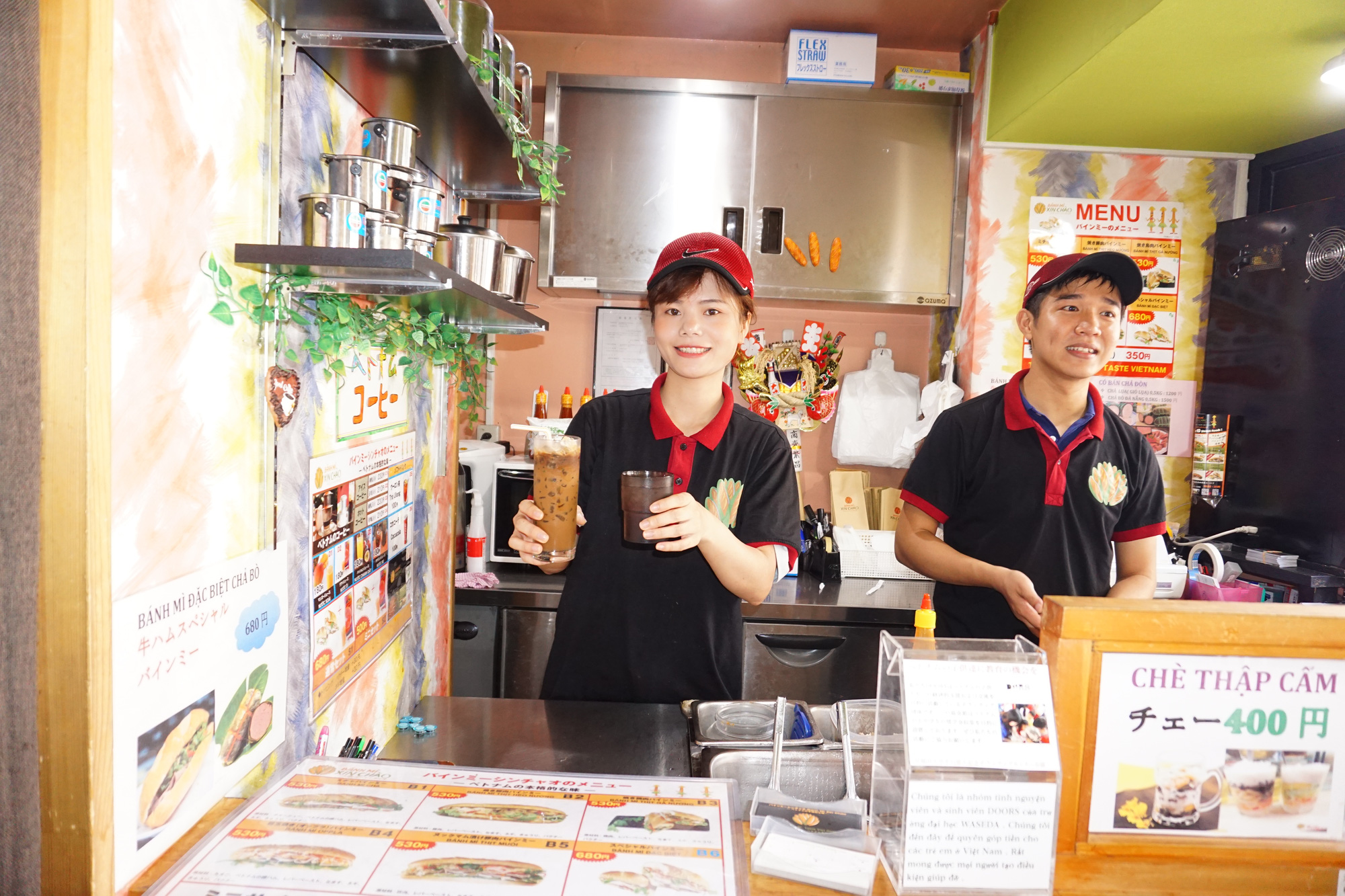 Bui Thanh Tam (right) and his wife stand in a Banh Mi Xin Chao store in Tokyo, Japan. Tam's wife is holding a glass of 'ca phe sua da' (Vietnamese-styled iced coffee with condensed milk). Photo: Cong Nhat / Tuoi Tre