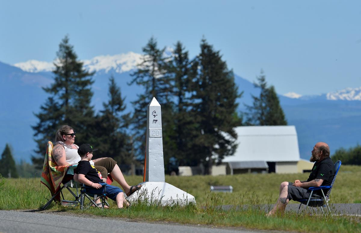 Jessica Boyer and 8-year-old Parker Holbeche sit across from Doug Boyer at a border marker during  Mother's Day along the Canada-U.S. border, closed to non-essential travel due to coronavirus disease (COVID-19) restrictions in Langley, British Columbia, Canada May 10, 2020.  Photo: Reuters