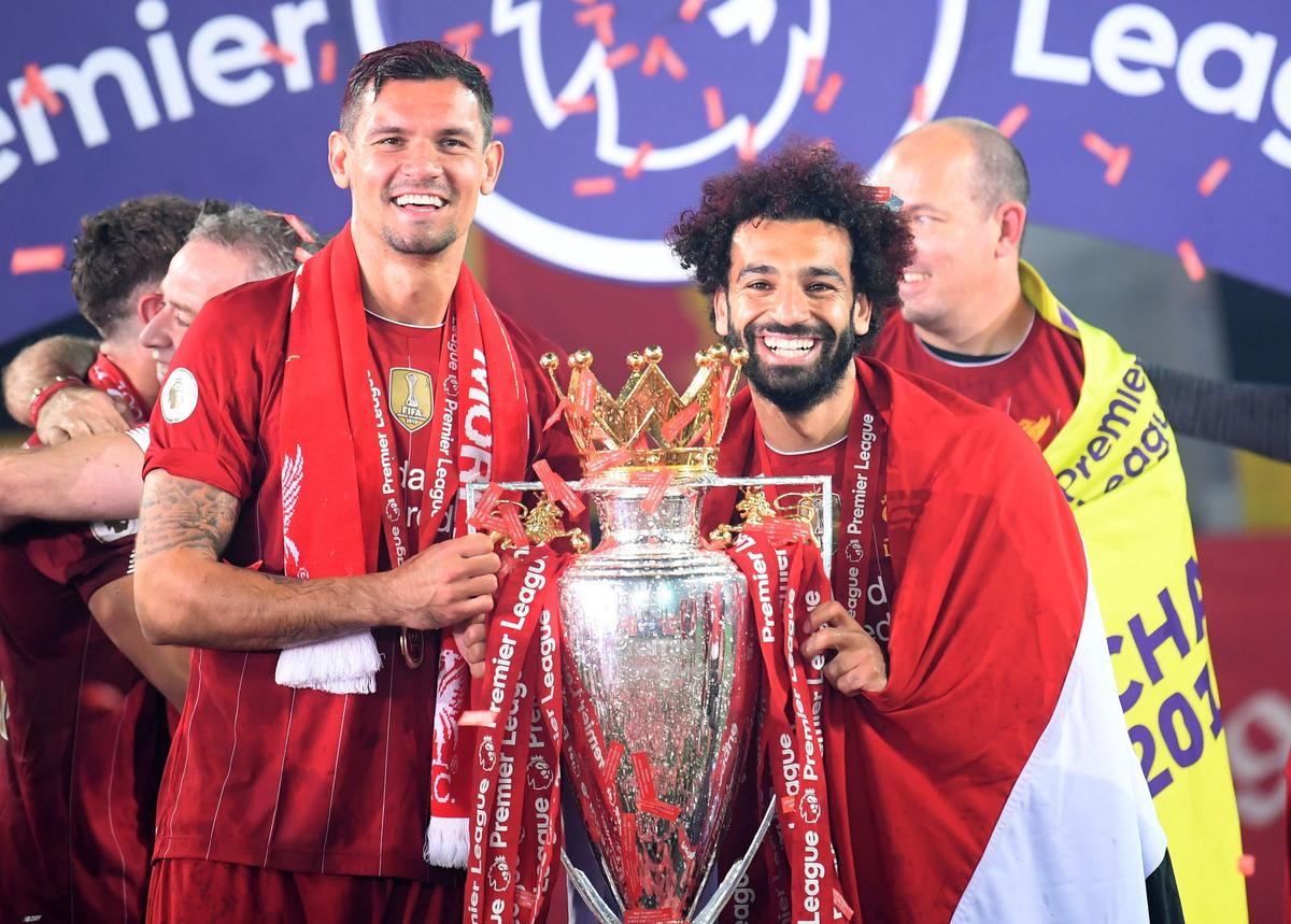 Liverpool's Dejan Lovren (left) and Mohamed Salah celebrate with the trophy after winning the Premier League Pool in Anfield, Liverpool, Britain, July 22, 2020. Photo: Reuters