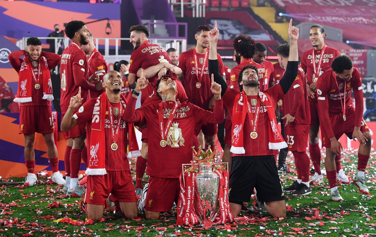 Liverpool's Alisson, Firmino and Fabinho celebrate with the trophy after winning the Premier League in Anfield, Liverpool, Britain, July 22, 2020. Photo: Reuters