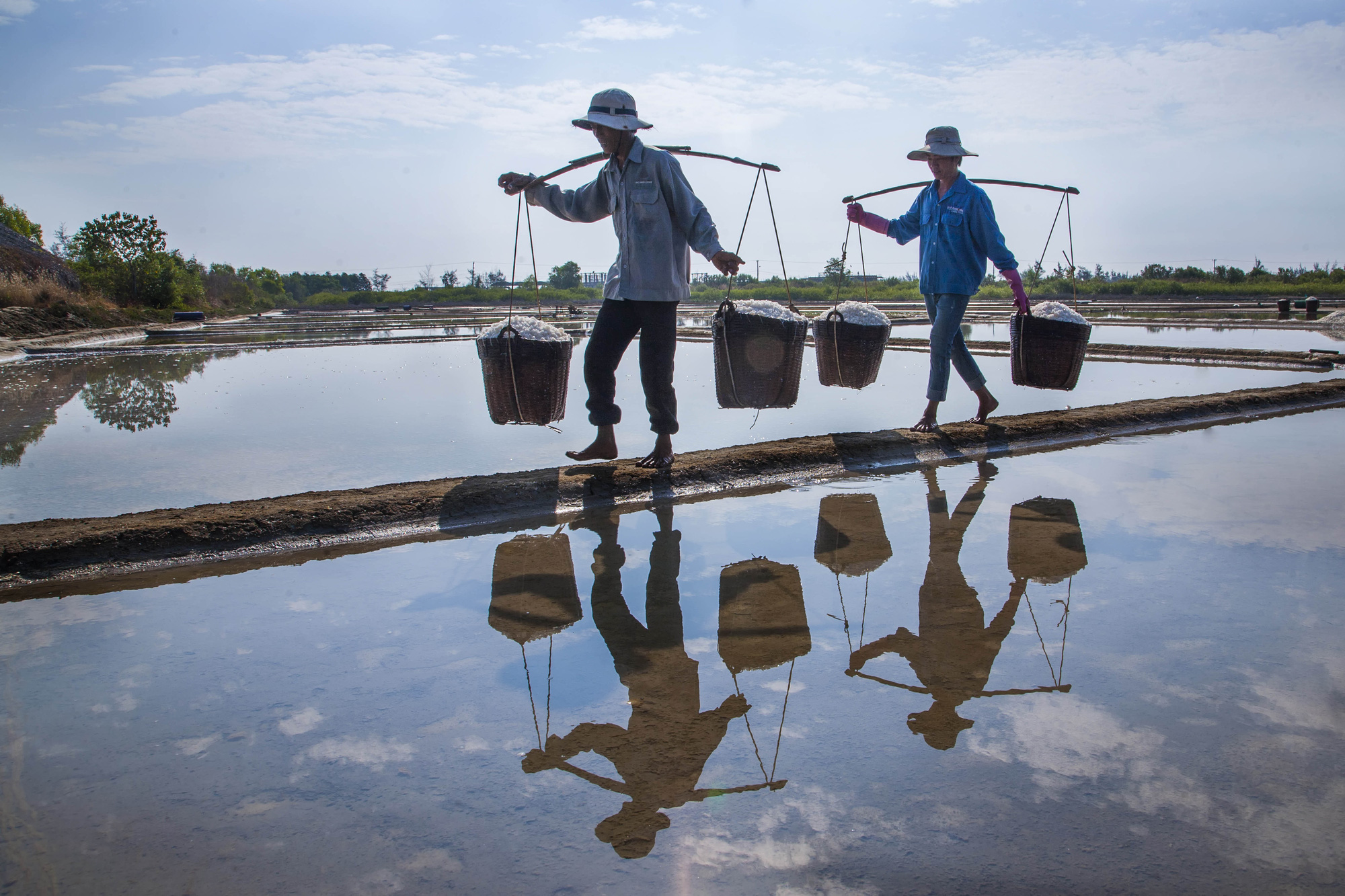 Two laborers carry salt at a salt field in Can Gio District, Ho Chi Minh City in this photo by Nguyen Manh Cuong, which won third prize at a local photo contest.