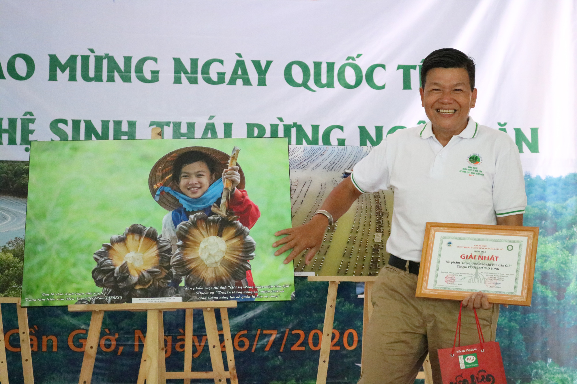 Photographer Tran Cao Bao Long poses for a photo next to his first-prize winning photo, which he said he had taken by chance during a trip to Can Gio District, Ho Chi Minh City. Photo: Anh Trinh / Tuoi Tre