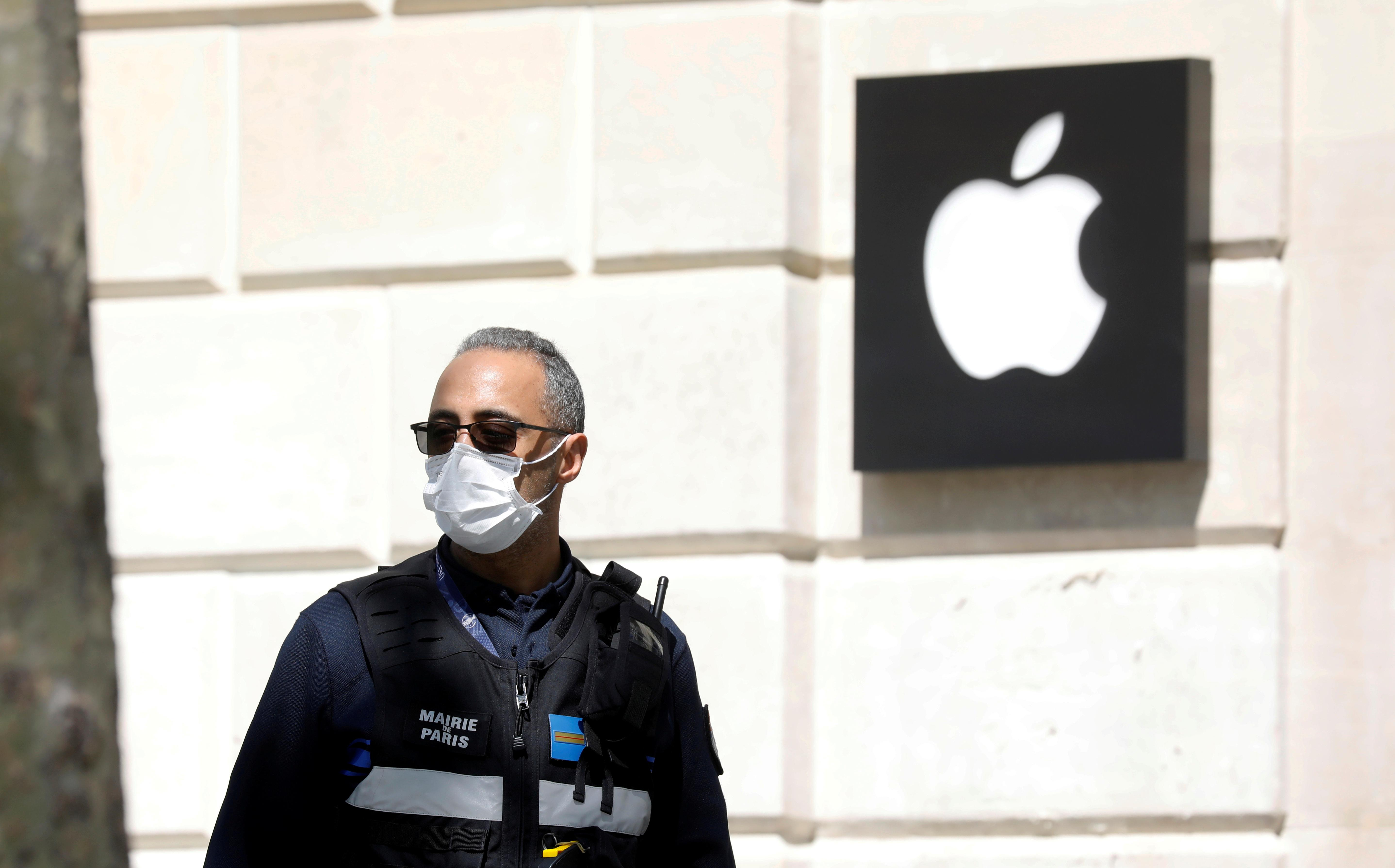 A municipal police officer wearing a protective face mask walks past the Apple store on the Champs-Elysees avenue in Paris in France, April 16, 2020. Photo: Reuters