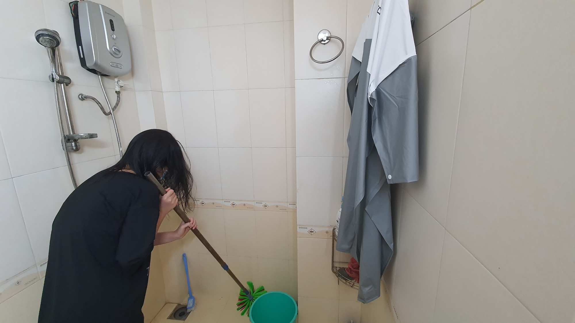 An hourly housekeeper cleans the bathroom of her employer in Ho Chi Minh City, Vietnam. Photo: Le Van / Tuoi Tre