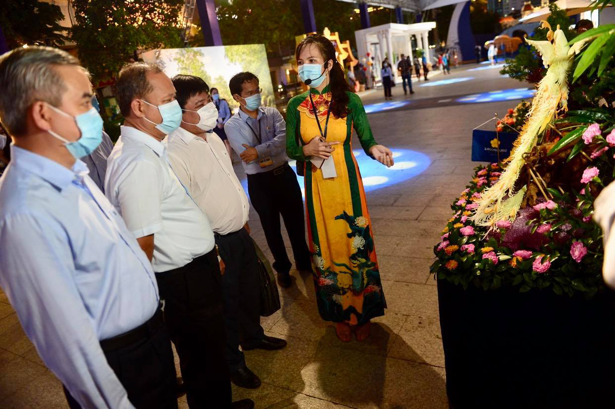Representatives of Tuoi Tre (Youth) newspaper and Saigontourist travel agency listen to a woman introducing photos at the exhibition 'Vietnam's 12 island districts – Now and then' at Nguyen Hue Walking Street in Ho Chi Minh City, Vietnam, July 31, 2020. Photo: Quang Dinh / Tuoi Tre