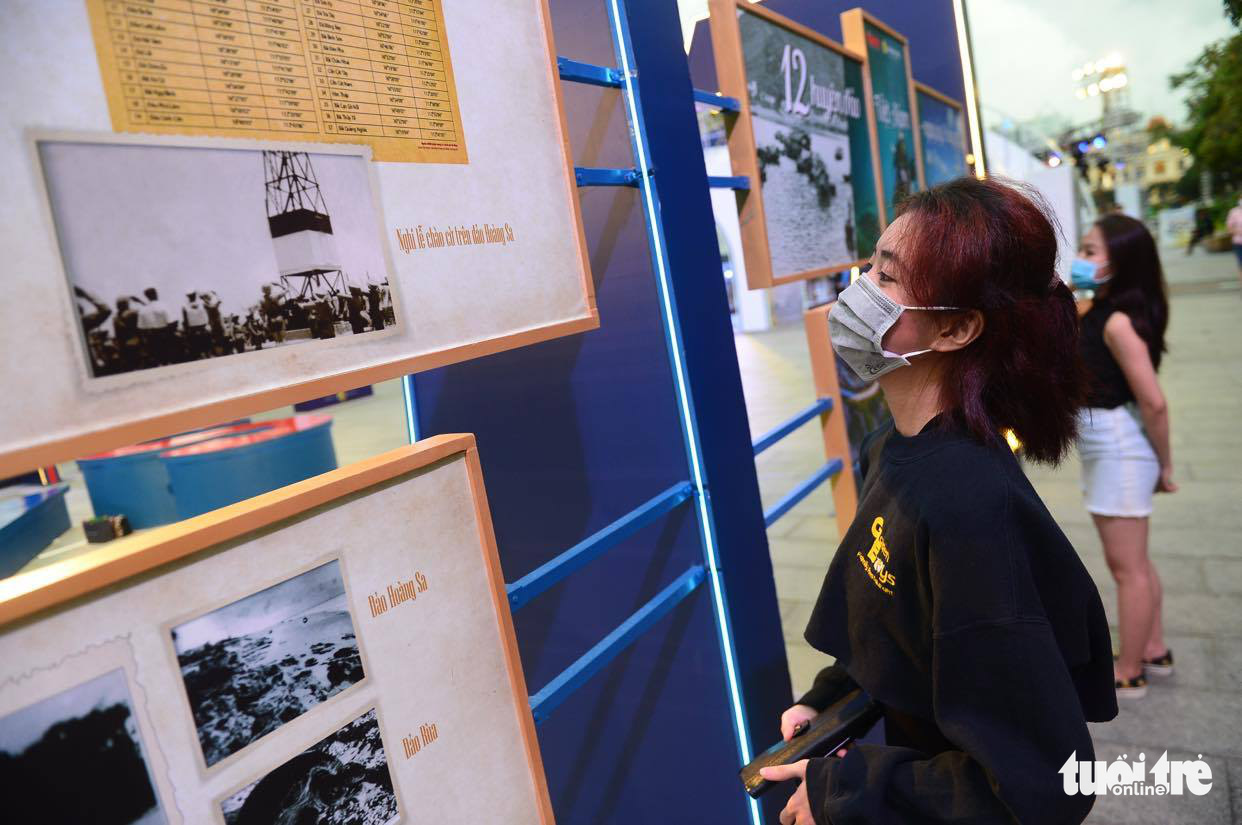 A woman, wearing face masks during the novel coronavirus disease (COVID-19) pandemic in Vietnam, looks at the photos at the exhibition 'Vietnam's 12 island districts – Now and then' at Nguyen Hue Walking Street in Ho Chi Minh City, Vietnam, July 31, 2020. Photo: Quang Dinh / Tuoi Tre