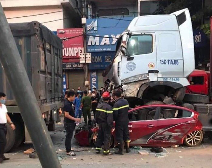 Officers investigate a crash site involving a car and trailer truck in Hanoi, August 4, 2020. Photo: Do Quang / Tuoi Tre