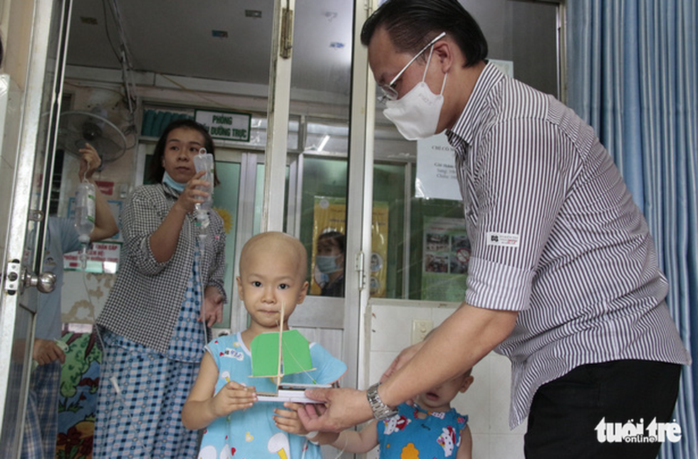 A child patient at the Ho Chi Minh City Oncology Hospital takes a ship model from Huynh Sang. Photo: Cong Trieu / Tuoi Tre