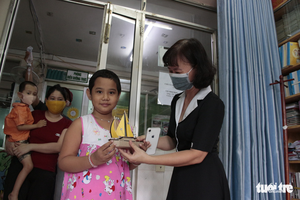 A child patient at the Ho Chi Minh City Oncology Hospital receives a ship model from a philanthropic supporter. Photo: Cong Trieu / Tuoi Tre