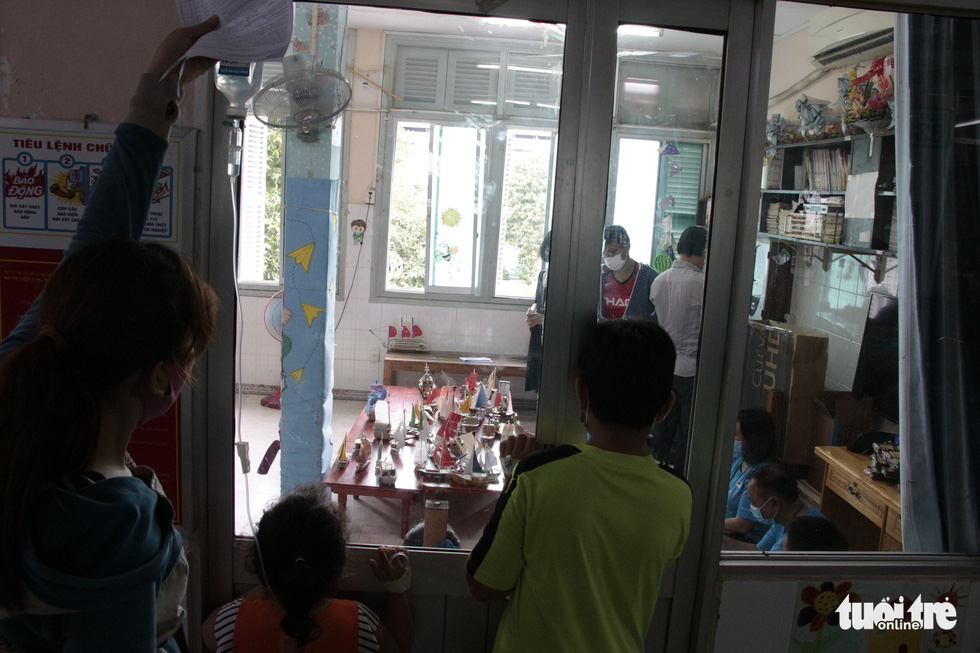 Child patients peek at ship models through the glass from the other side of the door in this photo taken at the Ho Chi Minh City Oncology Hospital. Photo: Cong Trieu / Tuoi Tre