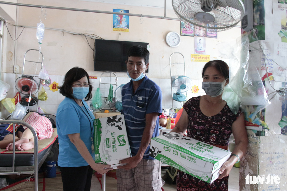 Parents of child cancer patients receive packages of milk from the philanthropic supporters. Photo: Cong Trieu / Tuoi Tre
