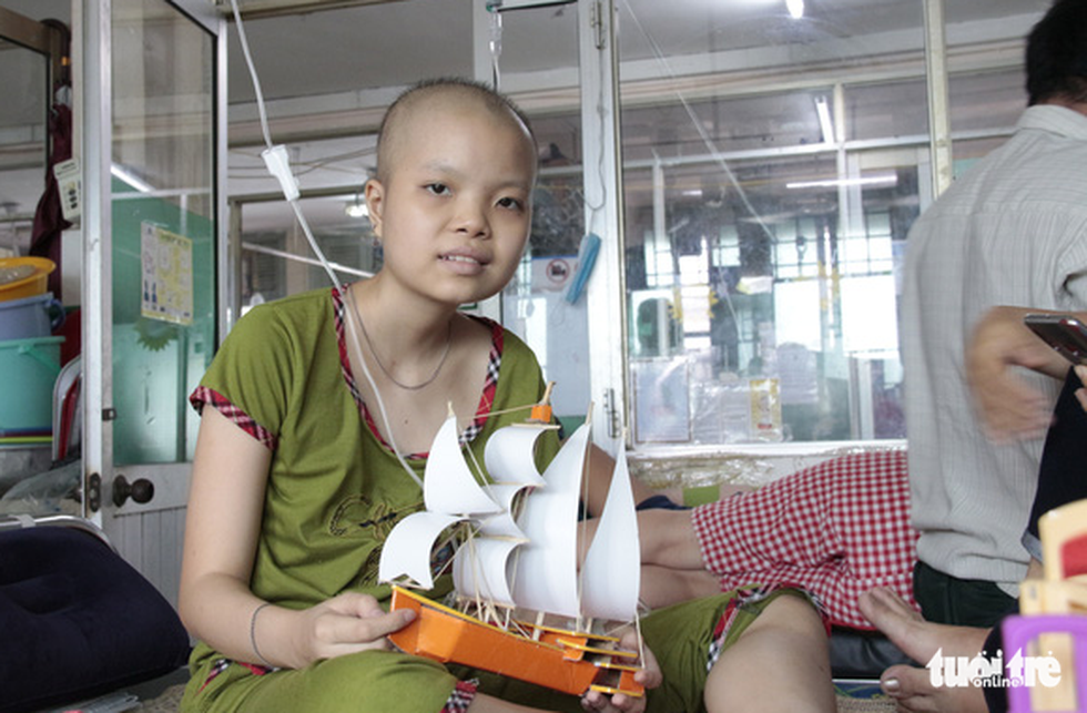 Tu Uyen, a child patient at the Ho Chi Minh City Oncology Hospital is seen with her ship model gift. Photo: Cong Trieu / Tuoi Tre