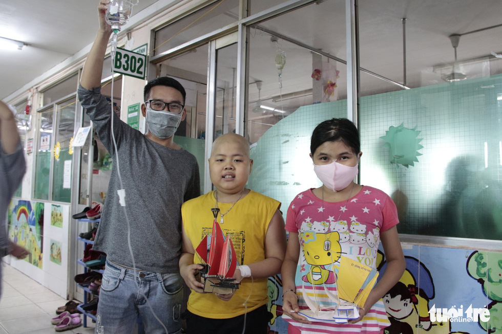 A child cancer patient (middle) holds a ship model gift. Photo: Cong Trieu / Tuoi Tre