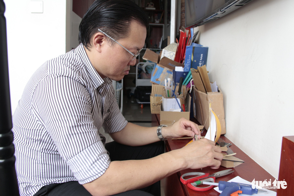 Huynh Sang is shown preparing ship models before gifting them to child cancer patients in this photo taken on July 31, 2020. Photo: Cong Trieu / Tuoi Tre