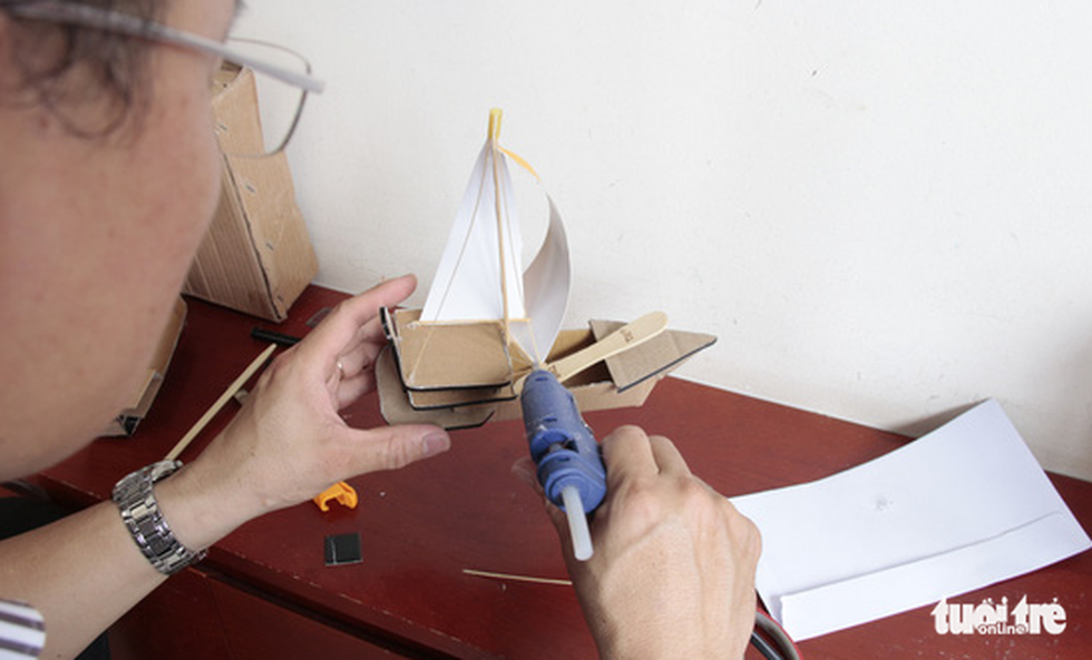 Sang is seen using a hot glue gun to craft his ship model. Photo: Cong Trieu / Tuoi Tre
