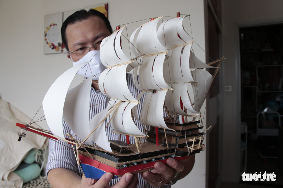 Sang holds one of his DIY ship models. Photo: Cong Trieu / Tuoi Tre