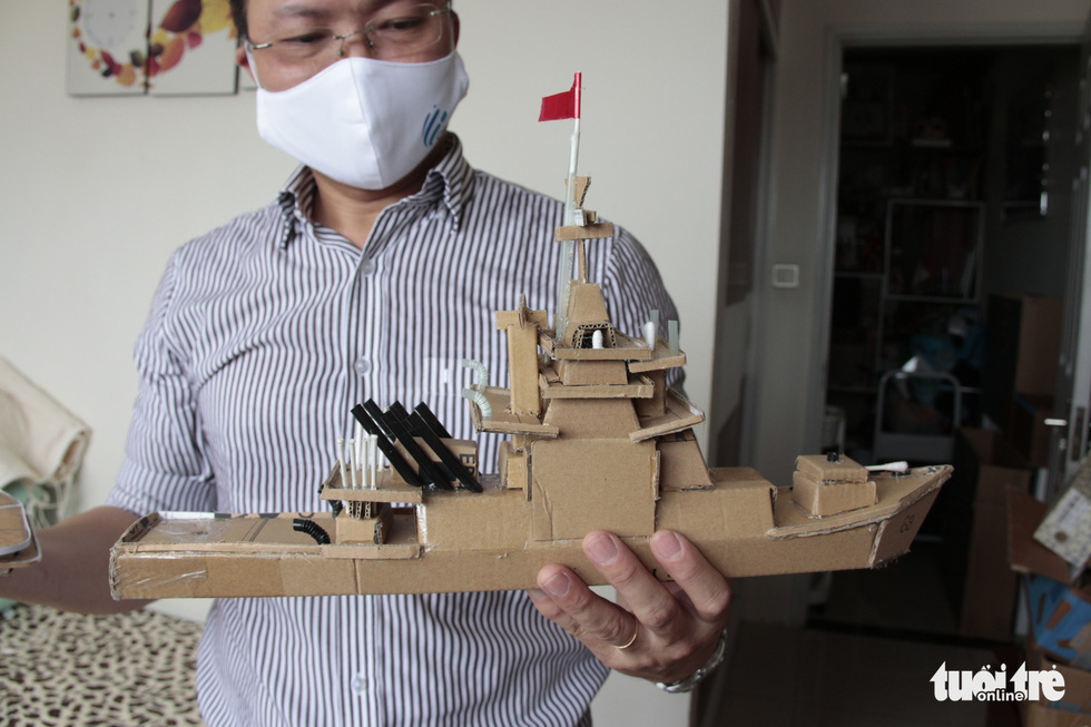 Sang holds a ship model replicating a battleship. Photo: Cong Trieu / Tuoi Tre