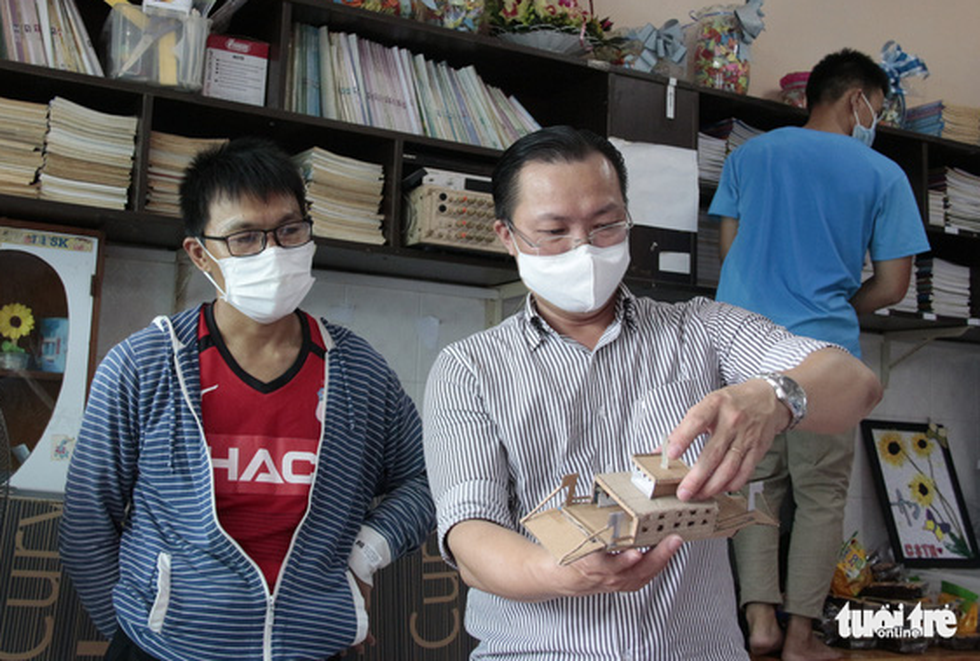 Sang (middle) is pictured completing one of his DIY ship models. Photo: Cong Trieu / Tuoi Tre