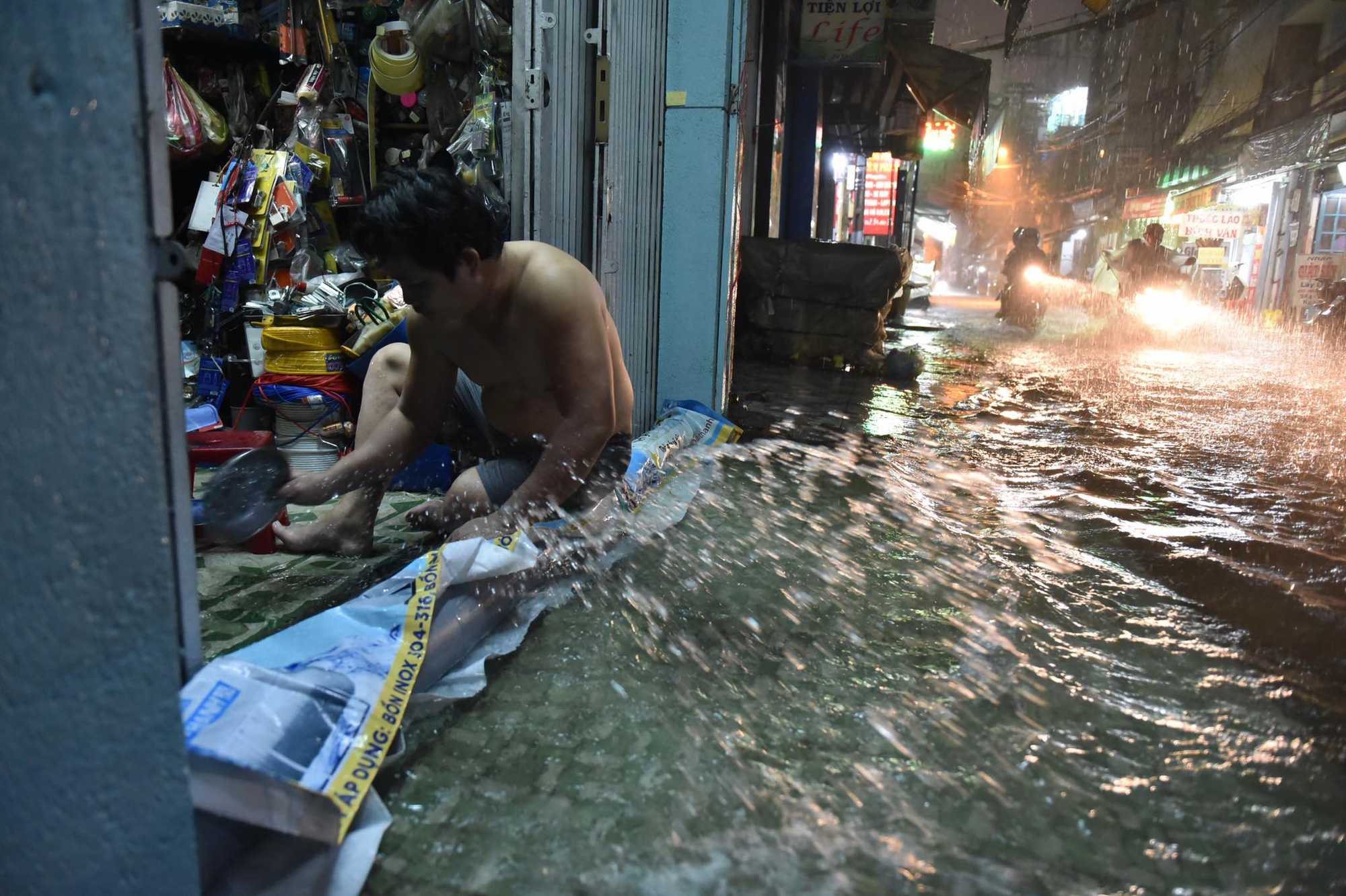 A man scoops rainwater from his house in Ho Chi Minh City, August 6, 2020. Photo: Ngoc Phuong / Tuoi Tre