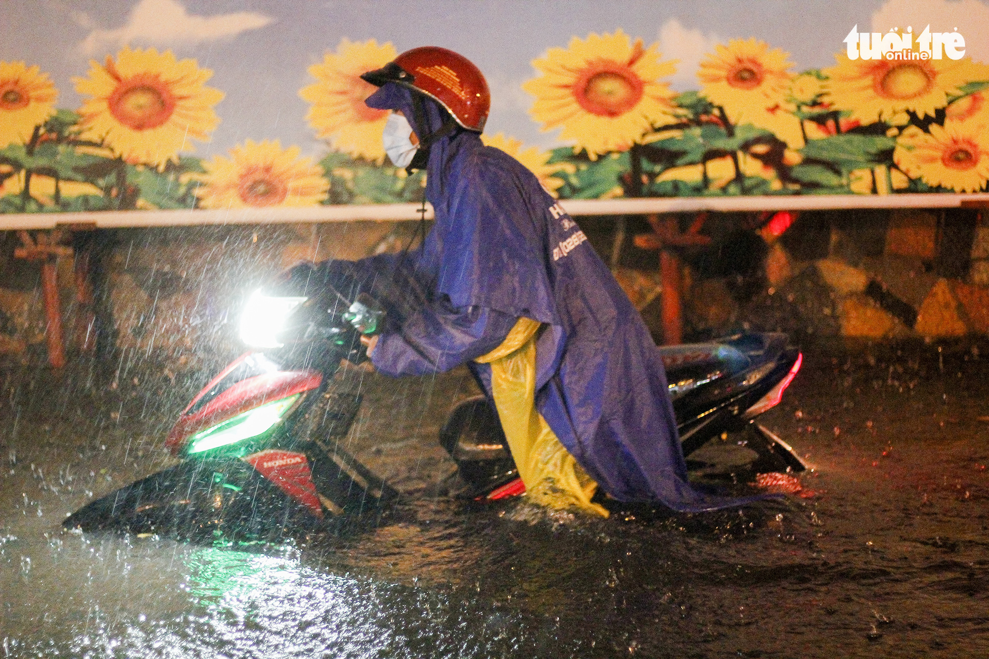 A resident pushes a motorcycle in knee-deep water, Ho Chi Minh City, August 6, 2020. Photo: Chau Tuan / Tuoi Tre