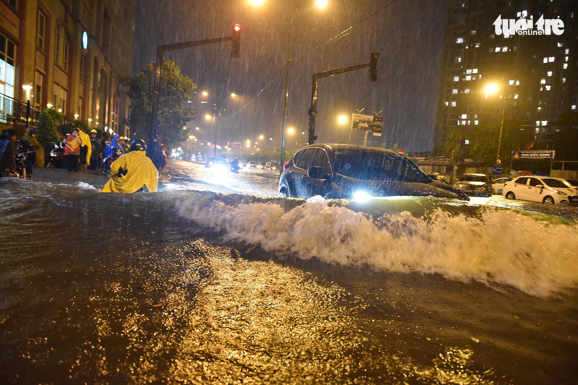 Waves of floodwater spill over as a car travels on an inundated street in Ho Chi Minh City, August 6, 2020. Photo: Ngoc Phuong / Tuoi Tre