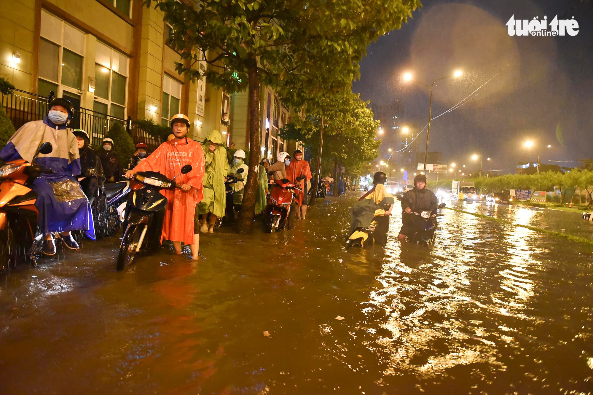 Motorcyclists wait for the floodwater to recede in Ho Chi Minh City, August 6, 2020. Photo: Tuoi Tre