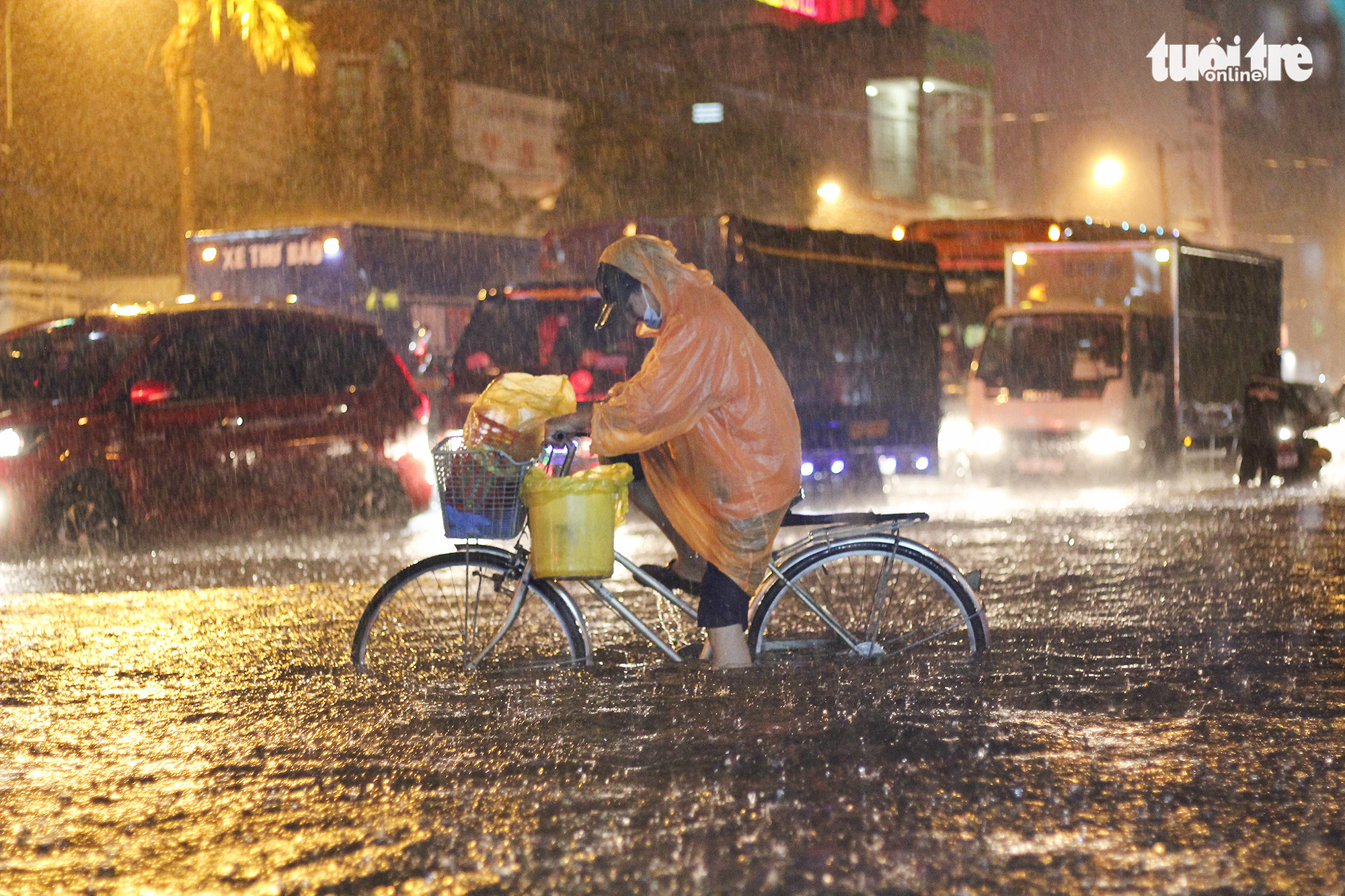 A resident has a hard time riding a bicycle in the heavy downpour that lashed Ho Chi Minh City on August 6, 2020. Photo: Chau Tuan / Tuoi Tre