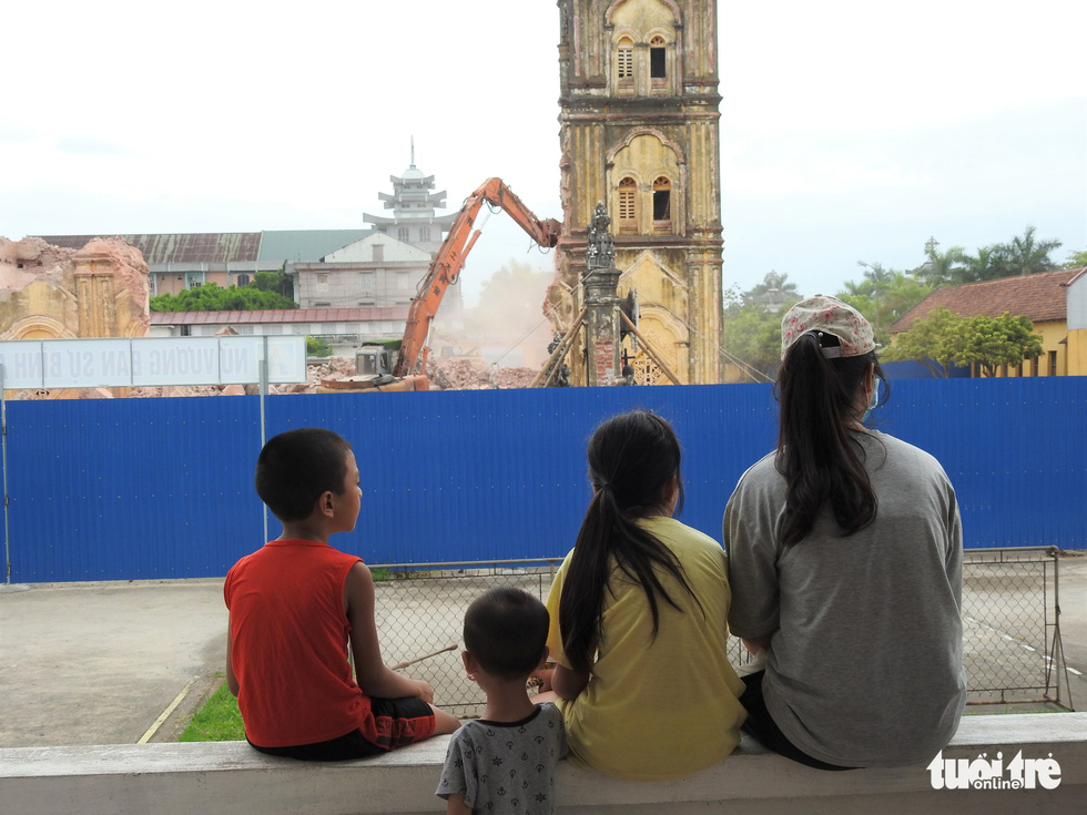 Local children watch the demolition of the two belfries at Bui Chu Cathedral in Nam Dinh Province, Vietnam, August 1, 2020. Photo: Thien Dieu / Tuoi Tre