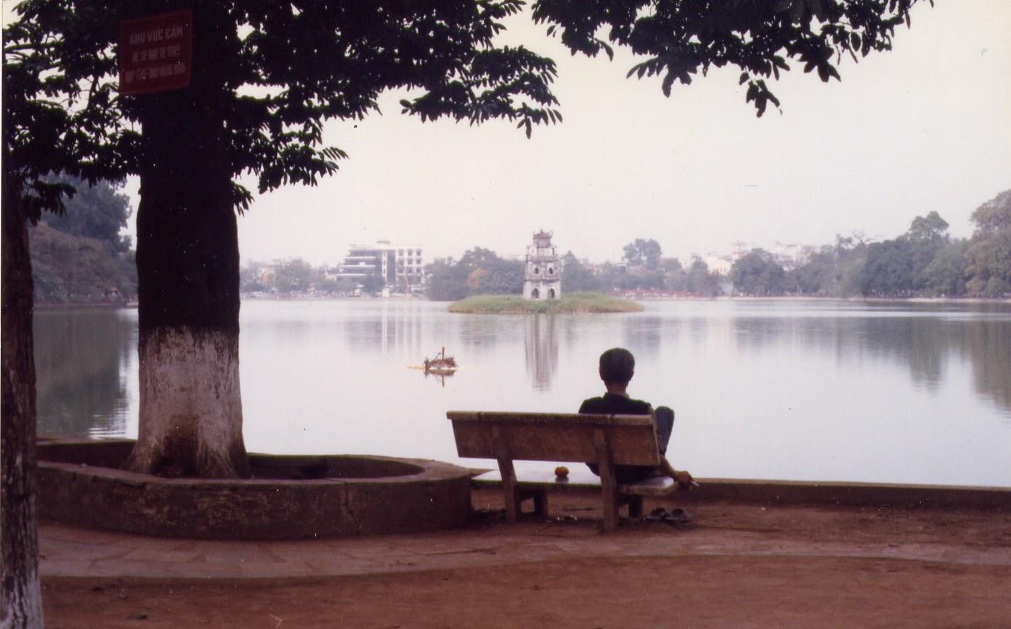 A man sits by Hoan Kiem Lake in Hanoi in 1997. Photo: Kyle Nunas