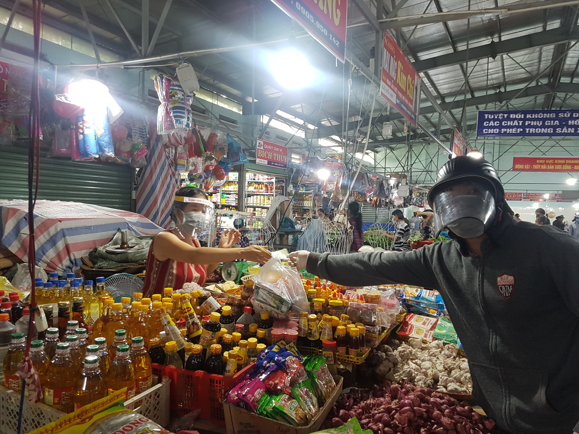 A merchant and buyer wear face masks and plastic shields at a market in Da Nang City, Vietnam, August 12, 2020. Photo: Huu Kha / Tuoi Tre