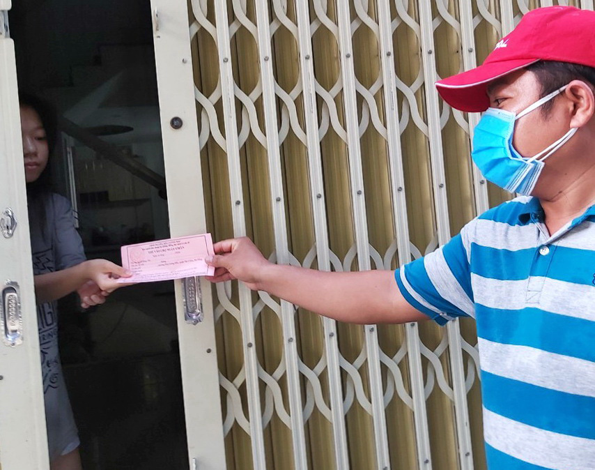 'Market access tickets' are handed to a resident in Da Nang City, Vietnam, August 11, 2020. Photo: D.C. / Tuoi Tre