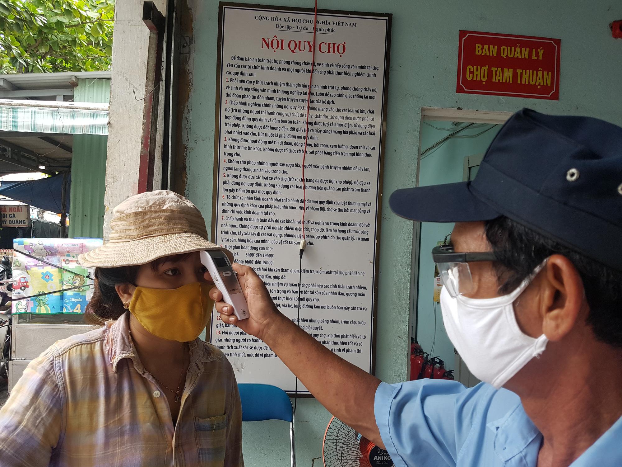 A woman has her body temperature measured before entering a market in Da Nang City, Vietnam, August 12, 2020. Photo: Huu Kha / Tuoi Tre
