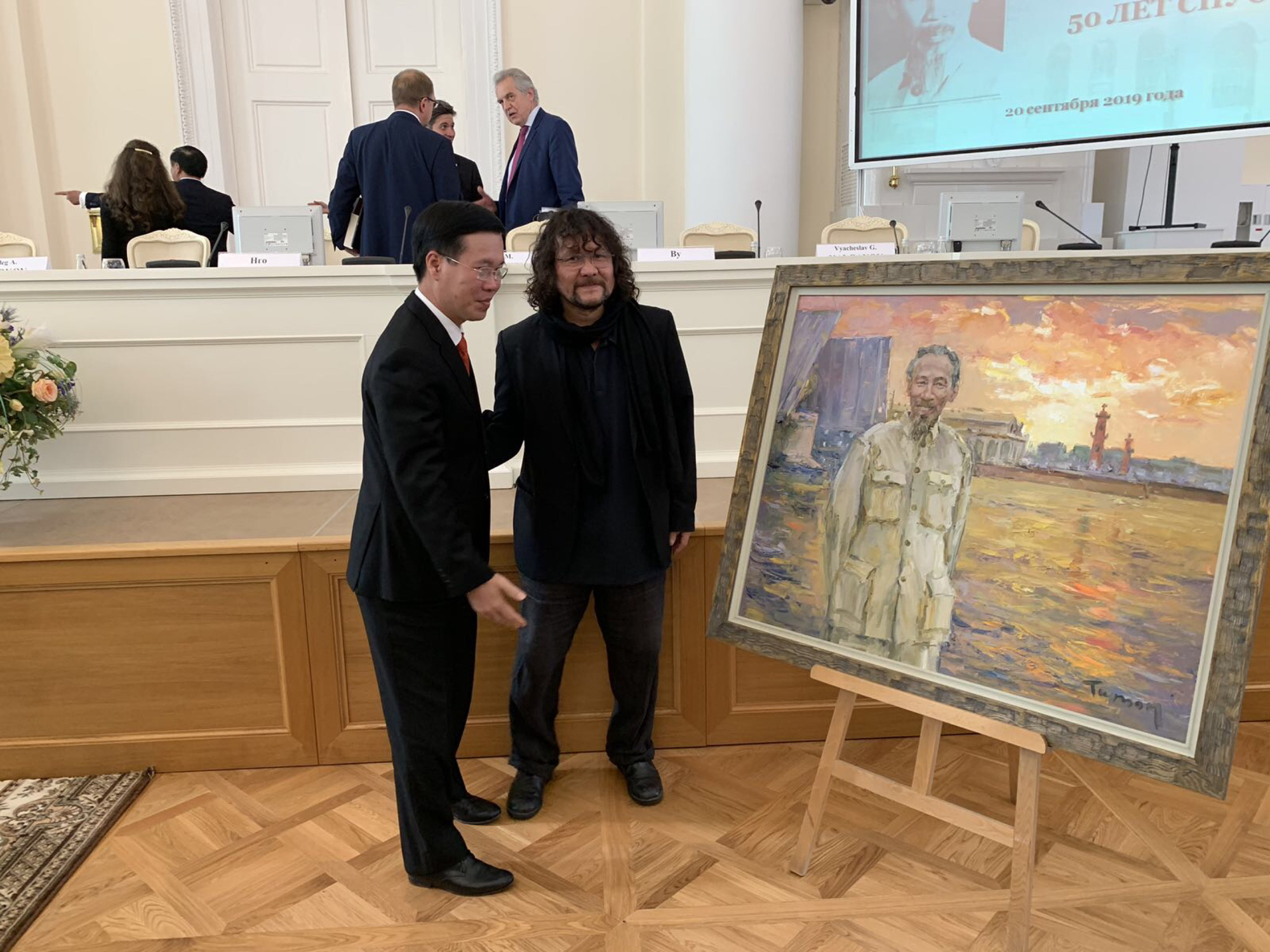 Russian artist Tuman Zhumabaev (right) and Vo Van Thuong, head of the Central Party Committee's Propaganda and Education, stand in front of one of Zhumabaev's paintings depicting late Vietnamese President Ho Chi Minh, which was presented as a gift to the delegation of Vietnamese leaders during their visit to Russia in this photo captured on February 20, 2019 and provided by Lilac gallery.