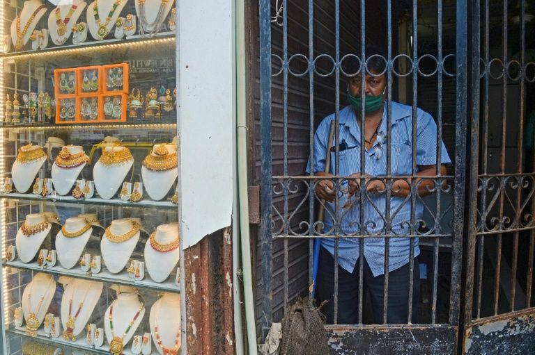 A guard stands behind an iron gate beside a gold jewellery shop in Mumbai. Photo: AFP