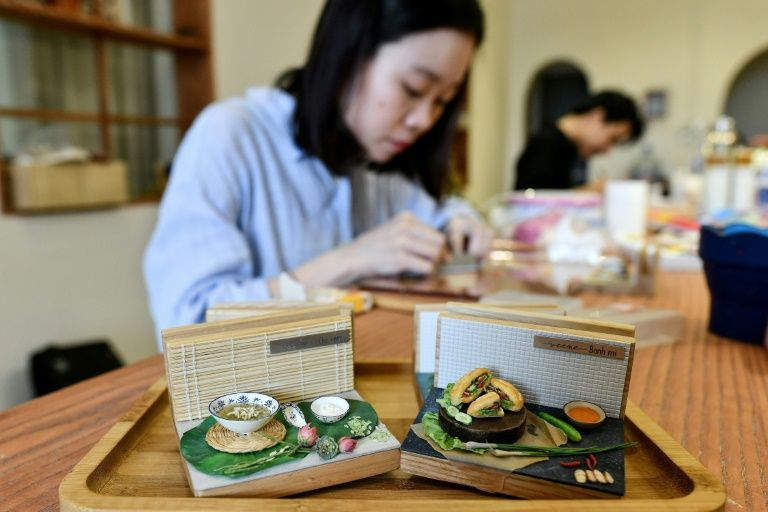 Nguyen Thi Ha An -- a 28-year-old architecture graduate -- who began crafting food miniatures a year ago, works at her studio in Hanoi, Vietnam. Photo: AFP