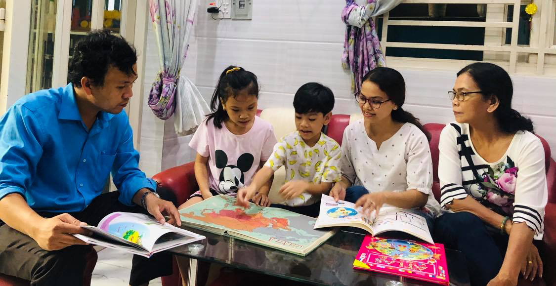 Thai Huynh Chi Kien (center) reads an atlas while being surrounded by his family in this photo taken at his home in Ho Chi Minh City. Photo: Phuong Nam / Tuoi Tre