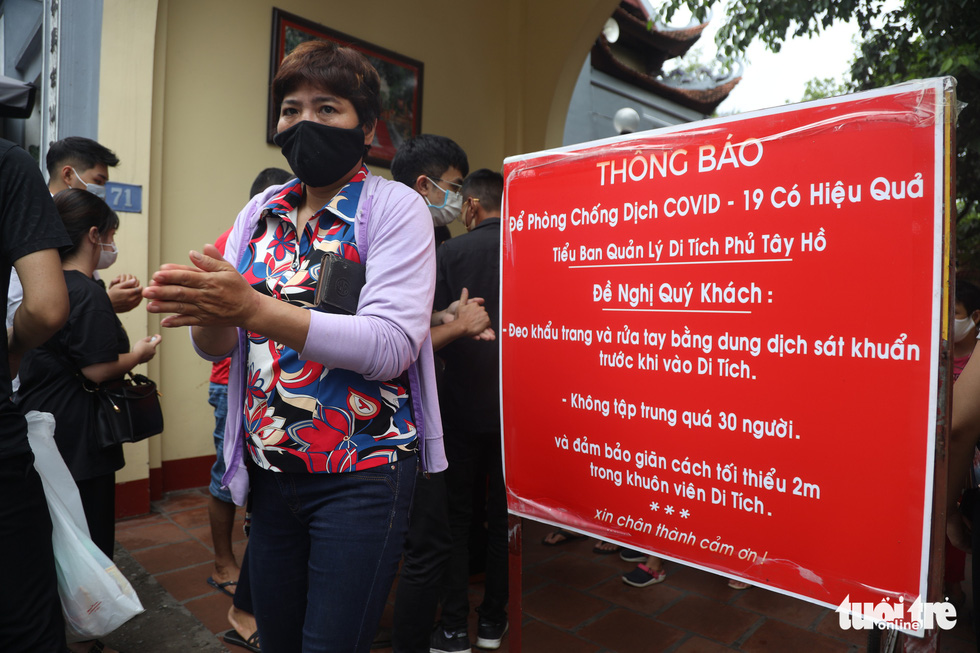 A notification board reminding visitors to practice safety measures to avoid novel coronavirus disease (COVID-19) is erected at an entrance to Tay Ho Temple in Tay Ho District, Hanoi, August 19, 2020. Photo: Mai Thuong / Tuoi Tre
