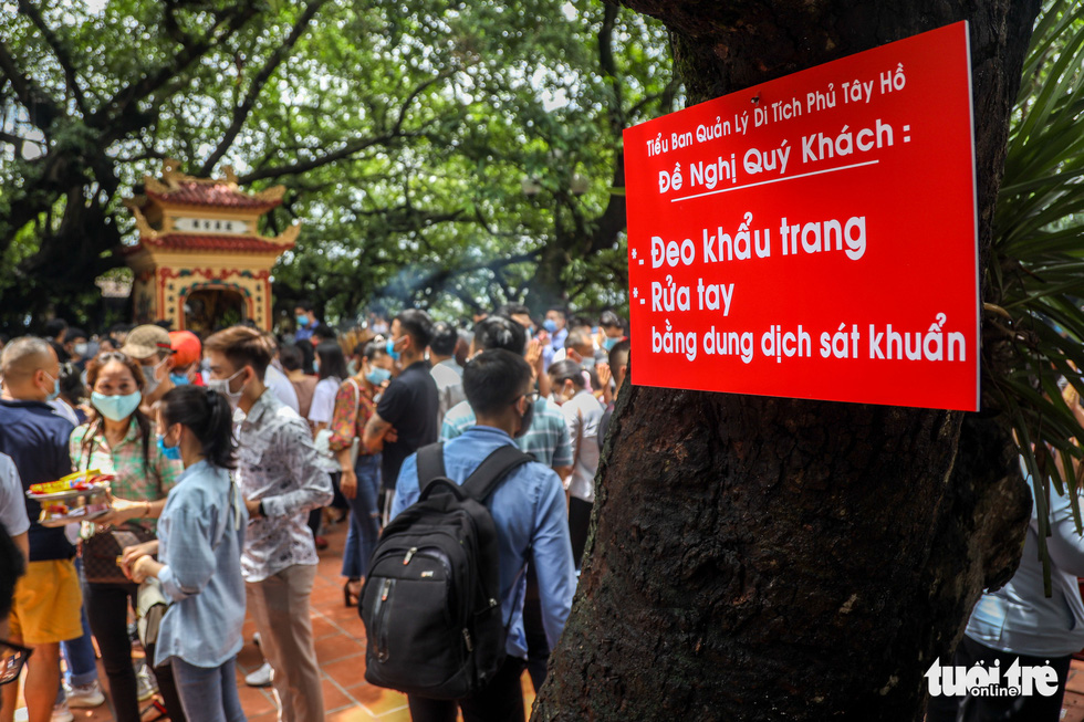 A notification board reminding visitors to practice safety measures to avoid novel coronavirus disease (COVID-19) is hung on a tree at Tay Ho Temple in Tay Ho District, Hanoi, August 19, 2020. Photo: Mai Thuong / Tuoi Tre