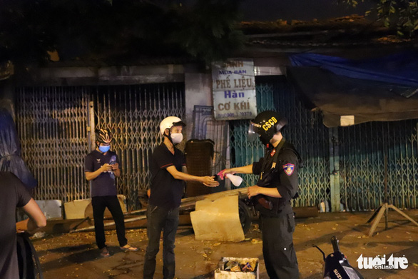 Team members of the 911 police unit in Da Nang adhere to hand sanitization rules during their work shift. Photo: Doan Cuong / Tuoi Tre