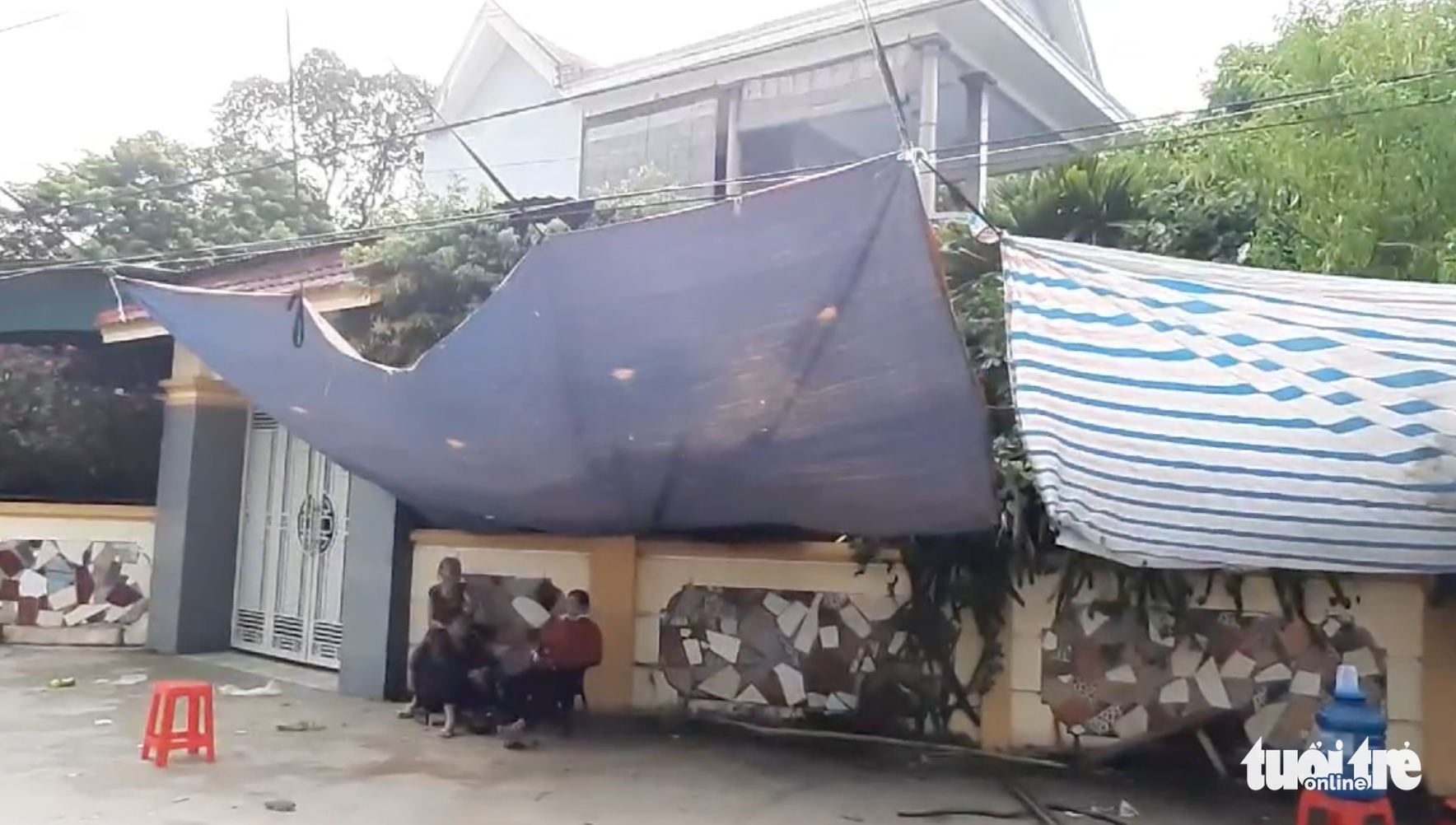 Ngo Thi Chung and her family members erect a tent in front of the house of a former police officer to pressure him into paying back  VND682 million (US$30,000) in debt in Thanh Chuong District, Nghe An Province, Vietnam. Photo: Doan Hoa / Tuoi Tre