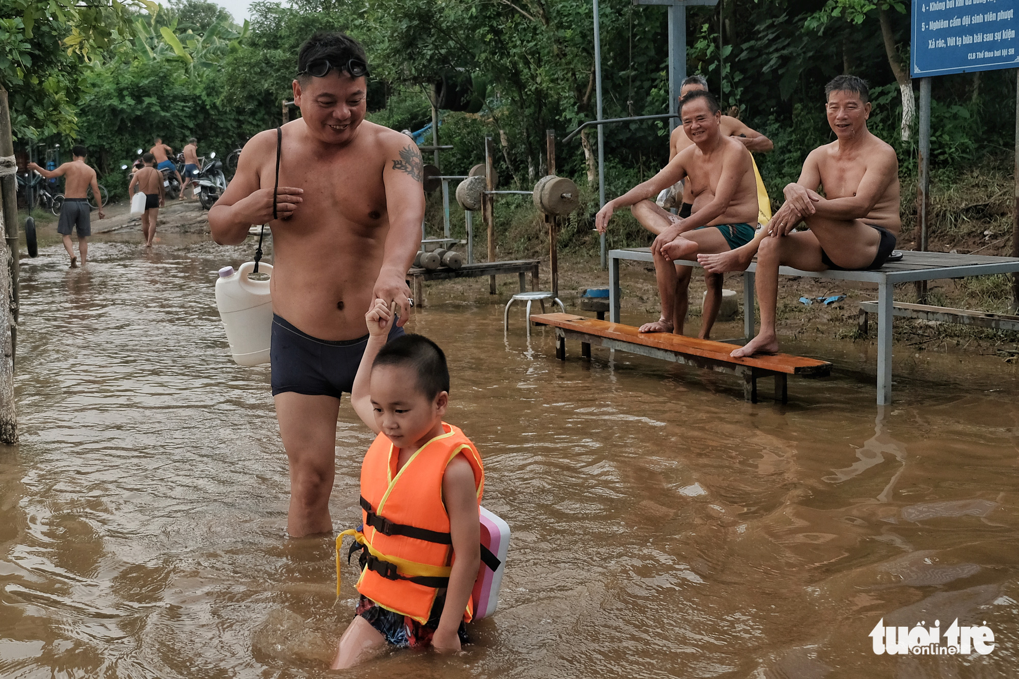 A man takes his child to the Hong River for a swim in Hanoi, August 22, 2020. Photo: Hoang Thanh Tung / Tuoi Tre