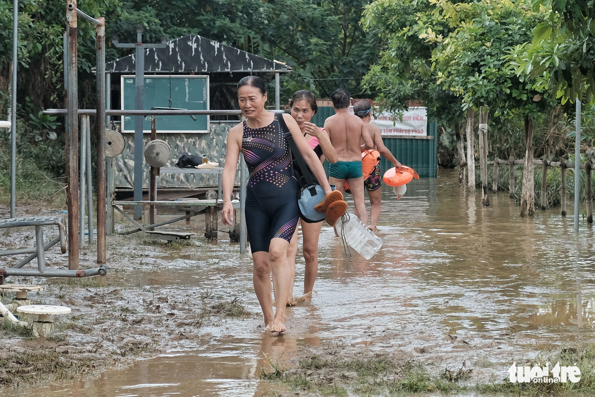 A woman uses a plastic canister as a lifebuoy while swimming in the Hong River in Hanoi, August 22, 2020. Photo: Mai Thuong / Tuoi Tre