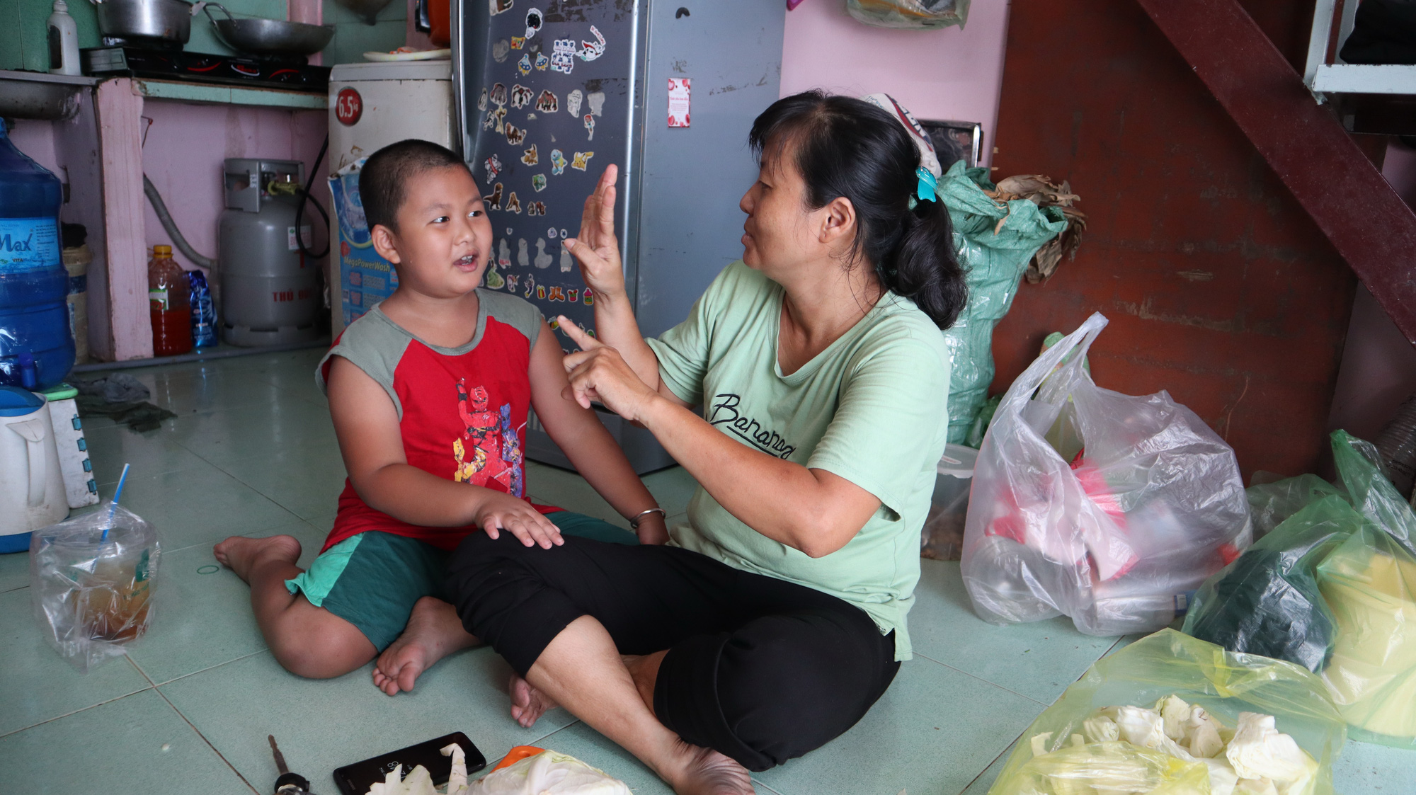 Le Mong Thuy (right), a deaf-mute food vendor, communicates with her son using sign language at their rented home in Binh Thanh District, Ho Chi Minh City, Vietnam. Photo: Le Van / Tuoi Tre