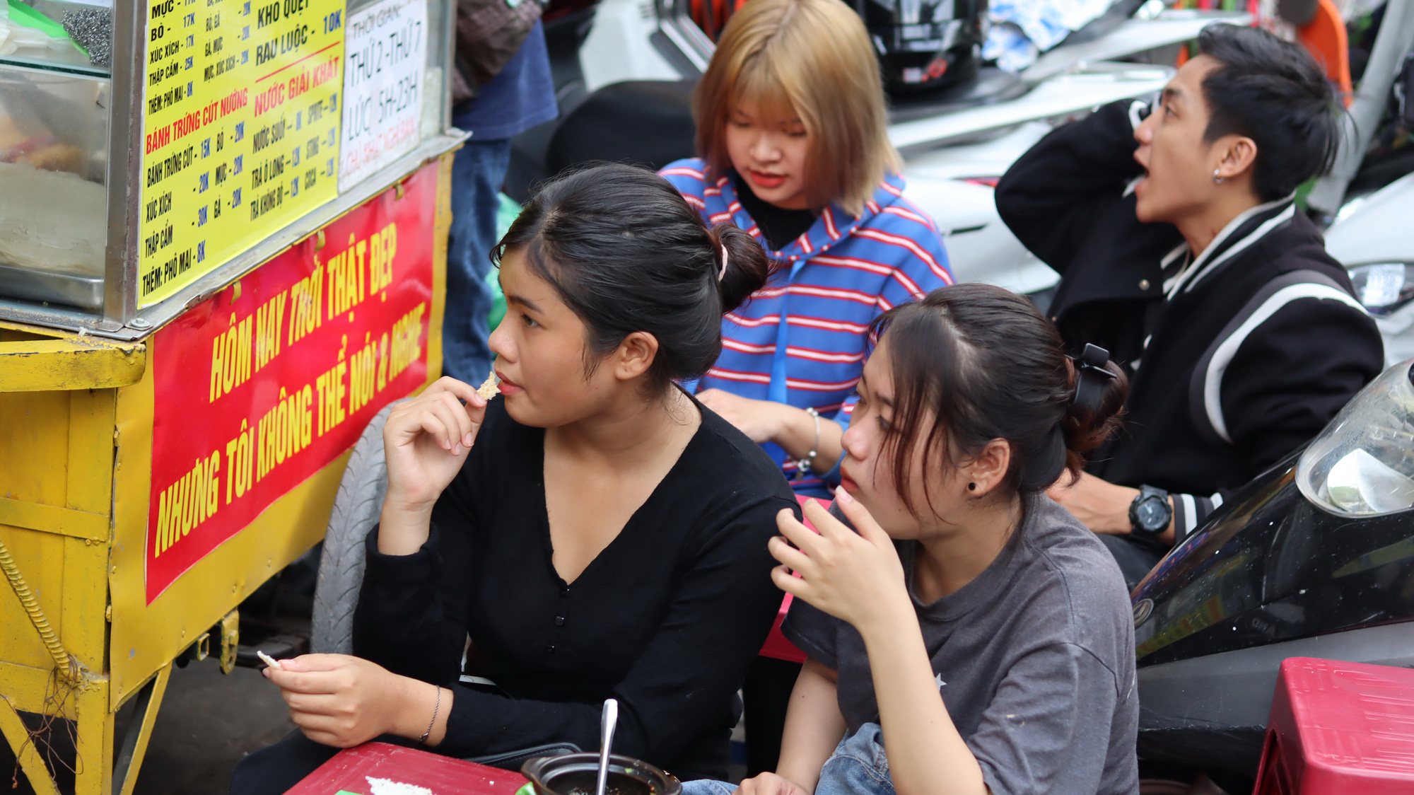 Young street food fans show interest in the savory snacks and the sign that reads 'The weather is really nice today, but I cannot speak or hear' at Le Truong Son and Le Mong Thuy's stall, placed in Binh Thanh District, Ho Chi Minh City, Vietnam. Photo: Le Van / Tuoi Tre