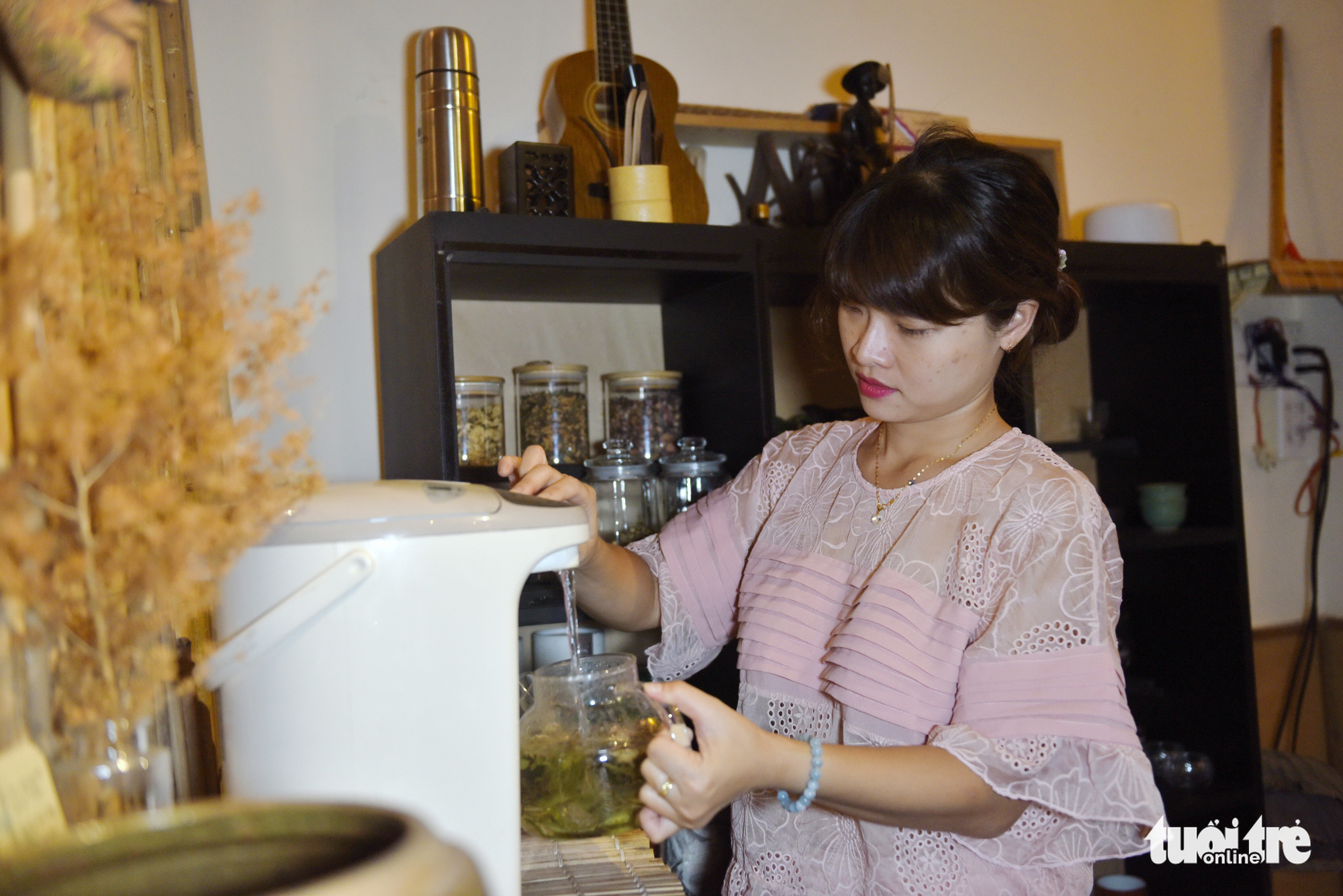 A customer fills a brewing vessel with hot water from an electric kettle to brew tea by herself at the Zentea teahouse in Ho Chi Minh City. Photo: Tuoi Tre