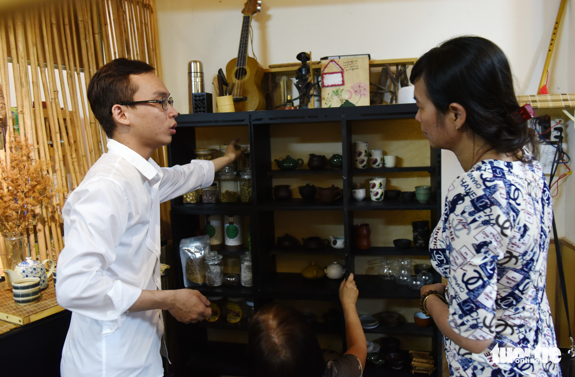 Duong Huu Thuan (left), member of the group that runs the Zentea teahouse in Ho Chi Minh City, introduces the different kinds of tea and how to brew them to a customer. Photo: Tuoi Tre