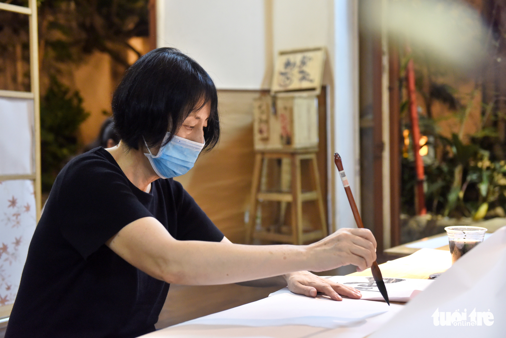 Koizumi, a Japanese customer, writes calligraphy at the Zentea teahouse in Ho Chi Minh City, Vietnam. She has taken the calligraphy class offered at the place for half of year. Photo: Tuoi Tre