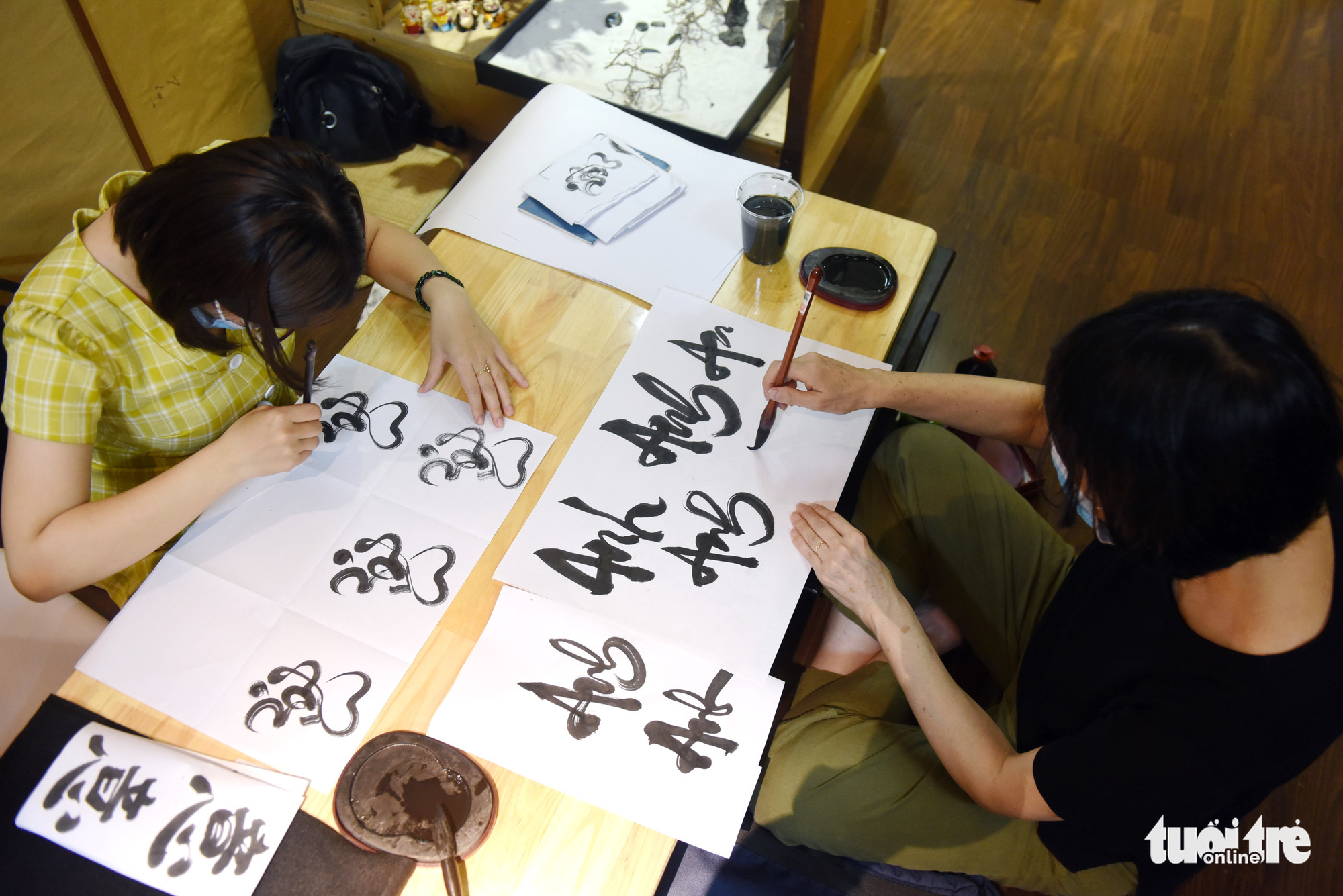 Two learners write calligraphy during a calligraphy class held every Thursday at the Zentea teahouse in Ho Chi Minh City, Vietnam. Photo: Tuoi Tre