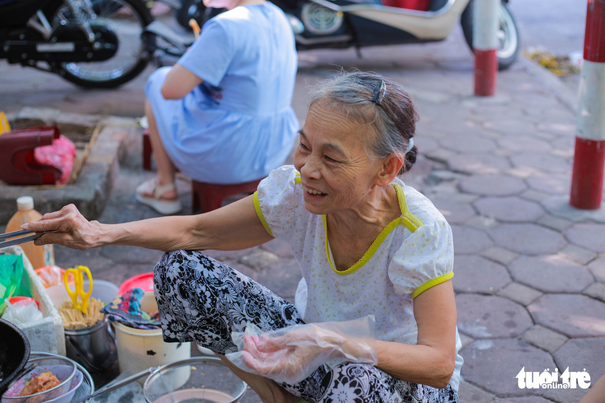 Nguyen Thi Thanh, 80, owner of a street food stall near Thanh Cong Secondary School in Hanoi, prepares food for customers. Photo: Hong Tham / Tuoi Tre